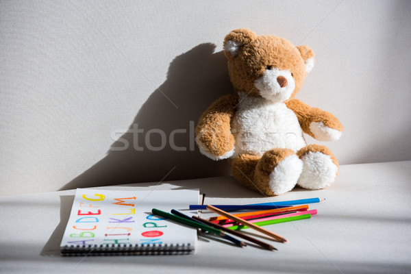 Stock photo: Teddy bear and drawing album with colorful pencils on grey