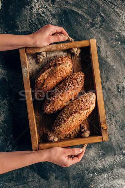 Stock photo: cropped shot of woman holding wooden box with loafs of bread in hands