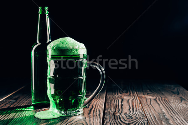 glass and bottle of green beer on wooden table, st patricks day concept Stock photo © LightFieldStudios