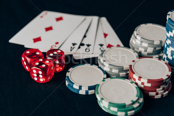 Dice with playing cards and chips on casino table Stock photo © LightFieldStudios