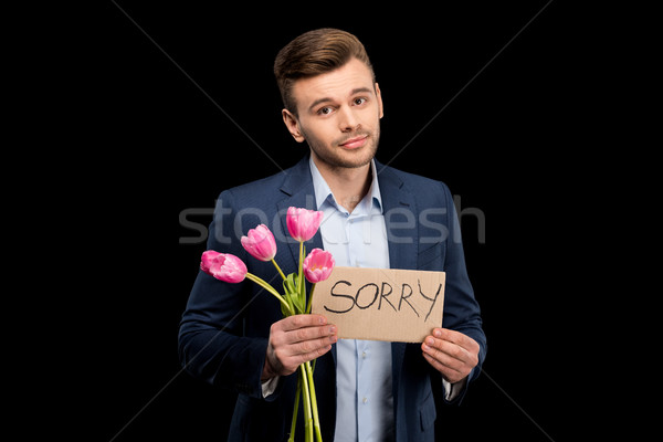 Handsome young man with pink tulips and sorry sign hopefully looking at camera Stock photo © LightFieldStudios
