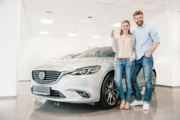 Happy couple with car key standing at car in dealership salon   Stock photo © LightFieldStudios