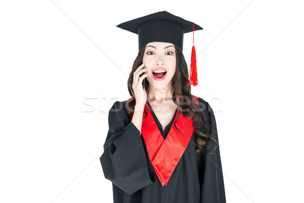 Surprised young brunette woman in mortarboard and academic gown looking at camera Stock photo © LightFieldStudios