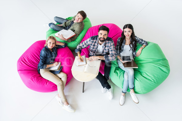 overhead view of students sitting on beanbag chairs and studying in studio on white  Stock photo © LightFieldStudios