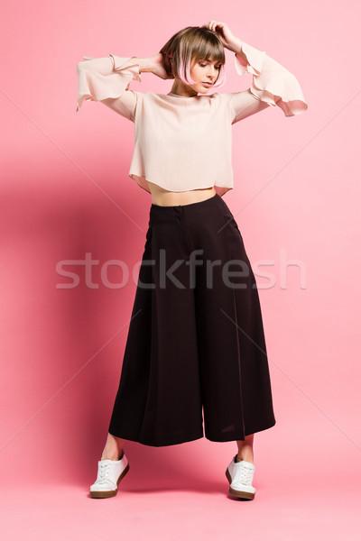 Divatos nő karok a magasban lövés fiatal nő ruházat Stock fotó © LightFieldStudios