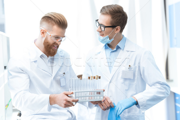 Young smiling men chemists in white coats holding test tubes in  Stock photo © LightFieldStudios