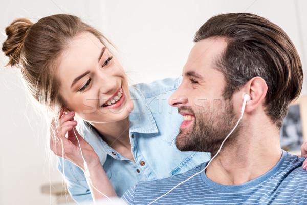 Mosolyog pár fülhallgató fiatal pér hallgat zene Stock fotó © LightFieldStudios