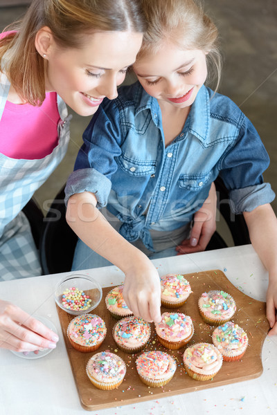 high angle view of daughter and mother decorating cupcakes Stock photo © LightFieldStudios