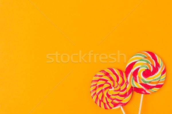 top view of sweet lollipops isolated on orange Stock photo © LightFieldStudios