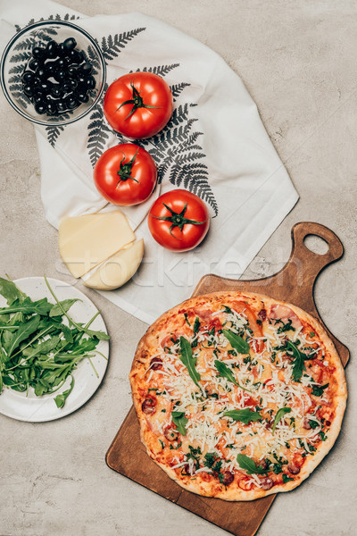 Delicious pizza on wooden cutting board and recipe ingredients on light background Stock photo © LightFieldStudios