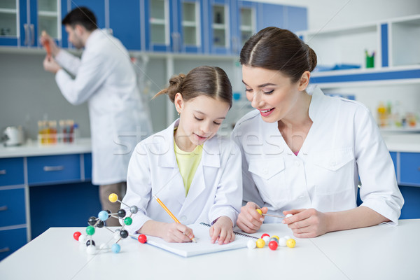 Smiling teacher and student scientists working with molecular model and taking notes Stock photo © LightFieldStudios