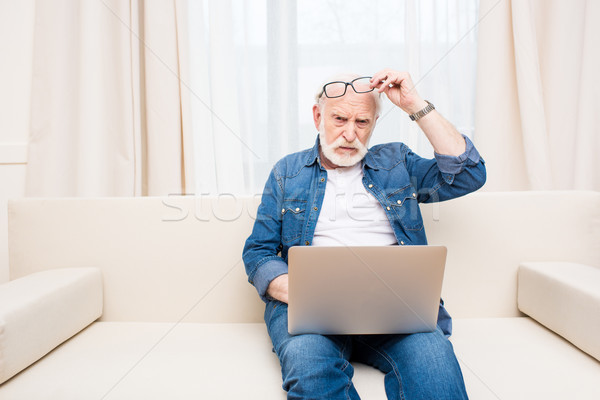 Frowning senior man with eyeglasses on forehead using laptop on sofa Stock photo © LightFieldStudios