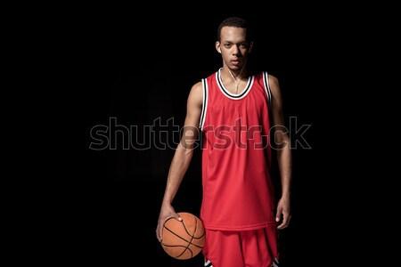 Young basketball player in earphones holding ball on black Stock photo © LightFieldStudios