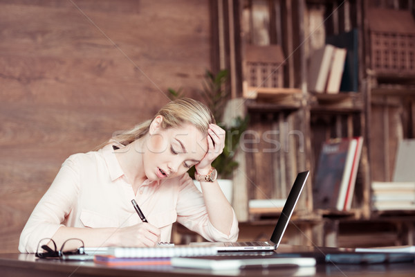 Young tired businesswoman using laptop and taking notes Stock photo © LightFieldStudios