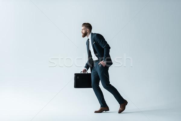 Oldalnézet jóképű szakállas üzletember fut aktatáska Stock fotó © LightFieldStudios