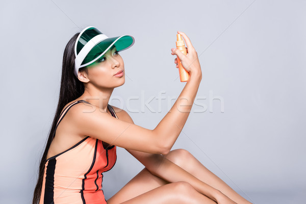 Stock photo: woman in swimsuit and visor with sunscreen bottle