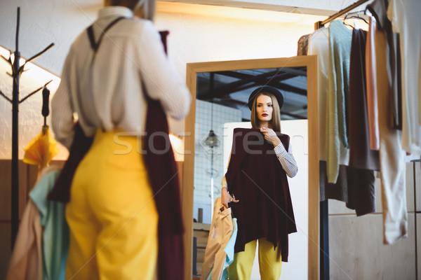 girl in hat choosing clothes  Stock photo © LightFieldStudios