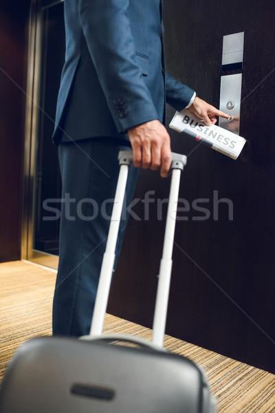 Biznesmen walizkę wzywając windy shot hotel Zdjęcia stock © LightFieldStudios