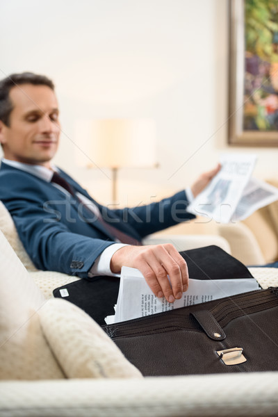 Businessman taking paperwork from briefcase Stock photo © LightFieldStudios