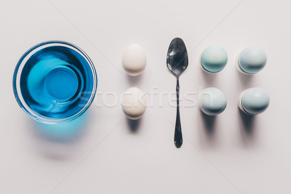 top view of glass with blue paint and chicken eggs on stands, easter concept Stock photo © LightFieldStudios
