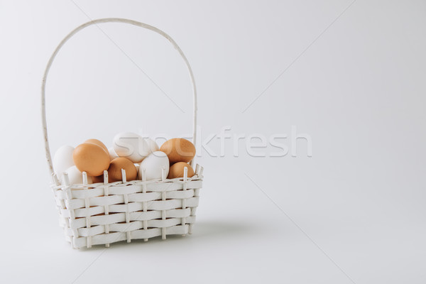 white and brown eggs laying in wicker basket on white background    Stock photo © LightFieldStudios
