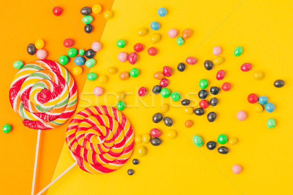 top view of lollipops and various candies on yellow and orange background Stock photo © LightFieldStudios