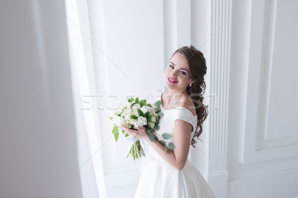 happy young bride posing in elegant white dress with wedding bouquet Stock photo © LightFieldStudios