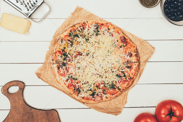 Stock photo: Pizza with cooking ingredients on white wooden background