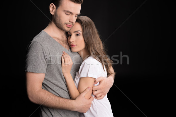 portrait of pensive woman bonding to man and looking away on black Stock photo © LightFieldStudios