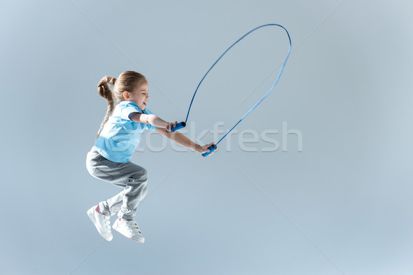side view of happy girl humping exercising with skipping rope on grey Stock photo © LightFieldStudios