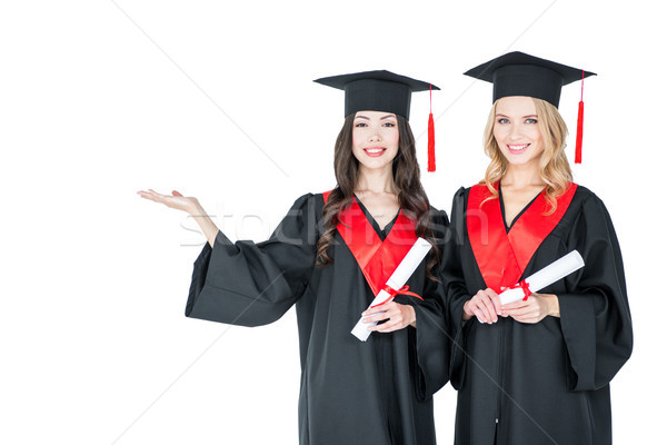 Two beautiful young students in academic caps holding diplomas and smiling at camera   Stock photo © LightFieldStudios