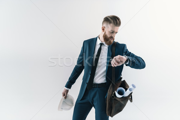 Stylish businessman with blueprints in shoulder bag checking wristwatch  Stock photo © LightFieldStudios