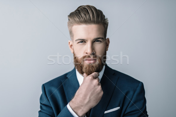 Stylish bearded businessman with hand on chin looking at camera Stock photo © LightFieldStudios