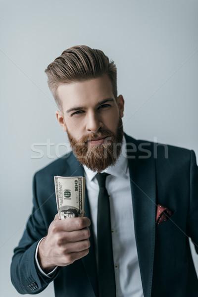 portrait of stylish businessman holding dollar banknotes on grey Stock photo © LightFieldStudios