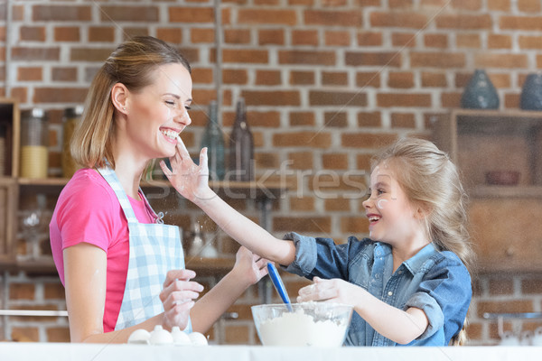 Stock photo: portrait of smiling mother and daughter having fun while cooking