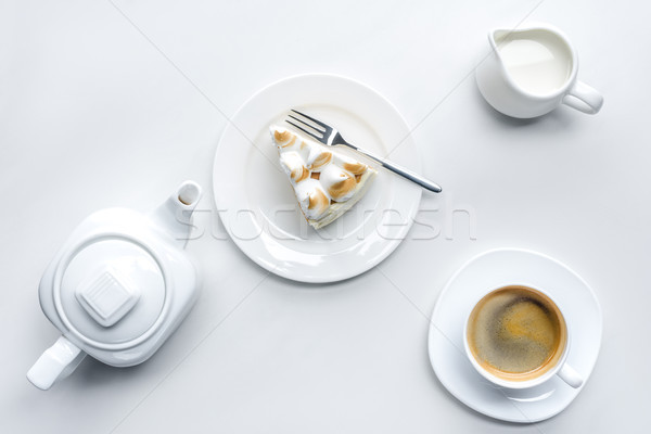 top view of appetizing piece of cake with meringue, teapot and coffee on white surface Stock photo © LightFieldStudios
