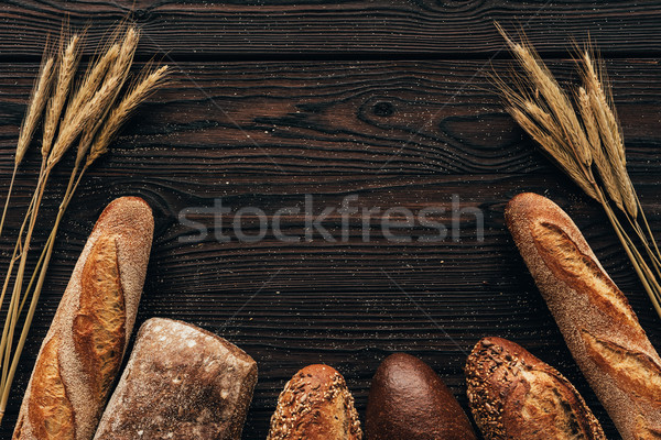 Stock photo: top view of arranged loafs of bread and wheat on wooden surface