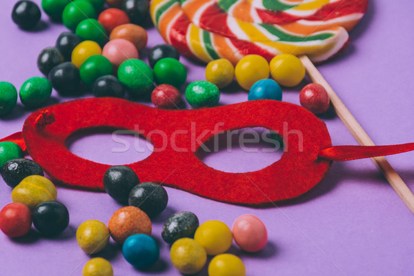 close up view of candies and masquerade mask isolated on purple Stock photo © LightFieldStudios