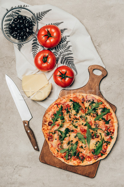 Whole pizza on wooden cutting board with tomatoes, cheese and olives on light background Stock photo © LightFieldStudios