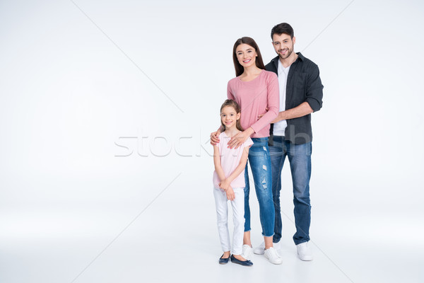 Happy young family with one child standing together and smiling at camera Stock photo © LightFieldStudios