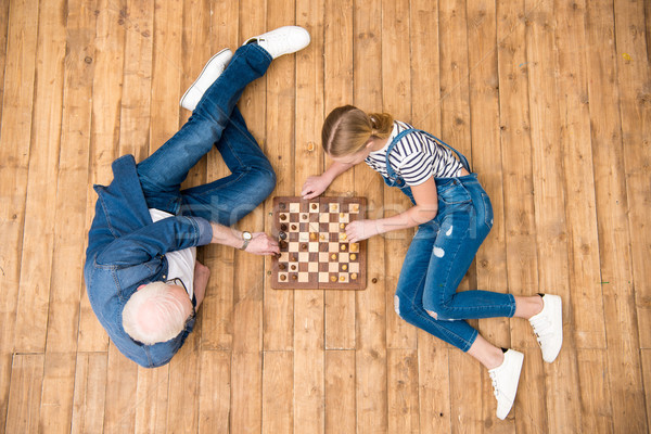Top view of grandfather and granddaughter playing chess on hardwood floor Stock photo © LightFieldStudios