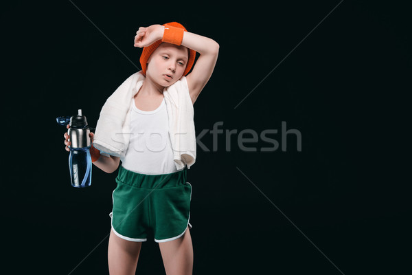 Tired boy in sportswear holding bottle with water and wiping sweat from forehead Stock photo © LightFieldStudios