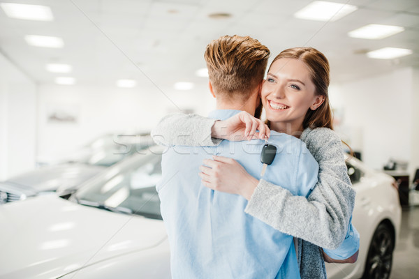 Happy couple holding car key and embracing in dealership salon    Stock photo © LightFieldStudios