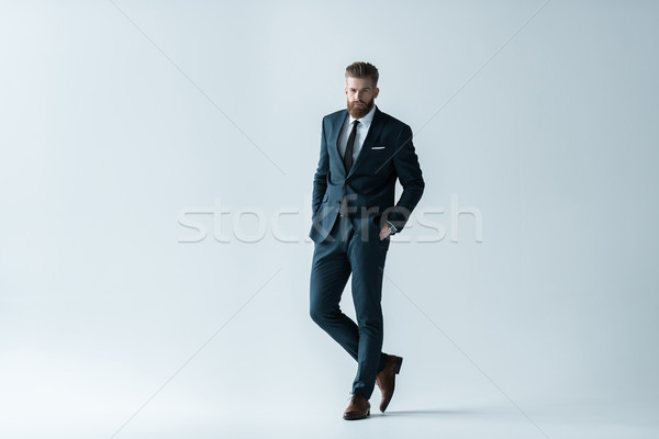 Confident bearded businessman in stylish suit standing with hands in pockets on grey Stock photo © LightFieldStudios