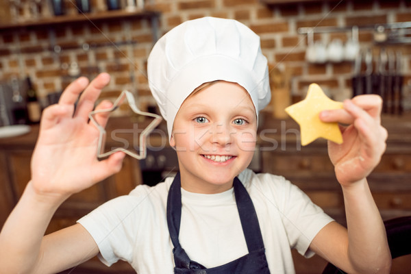 smiling boy holding raw star shaped dough and cookie cutter Stock photo © LightFieldStudios