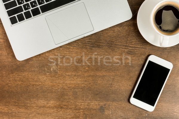Close-up view of laptop and smartphone with blank screen on wooden table top, wireless communication Stock photo © LightFieldStudios