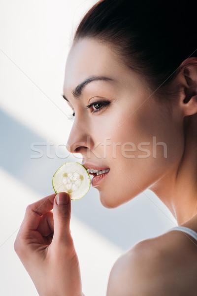 Nő eszik szelet uborka oldalnézet lövés Stock fotó © LightFieldStudios