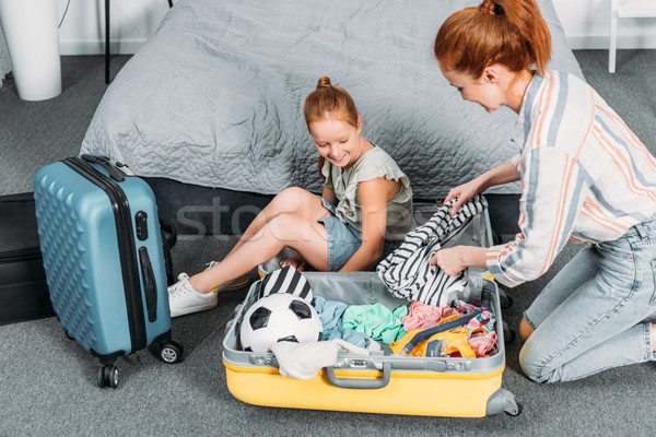mother and daughter packing clothes for trip Stock photo © LightFieldStudios