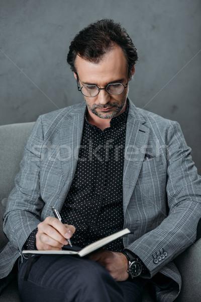 businessman taking notes in notebook Stock photo © LightFieldStudios
