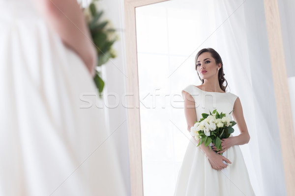 young bride in dress with wedding bouquet looking at her reflection in mirror Stock photo © LightFieldStudios